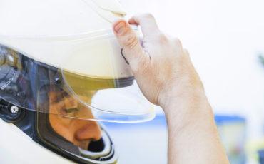 homem colocando um capacete de moto branco